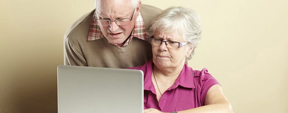 Elderly couple by a computer